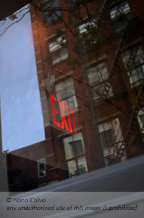 Exit sign reflected on window, SoHo, New York