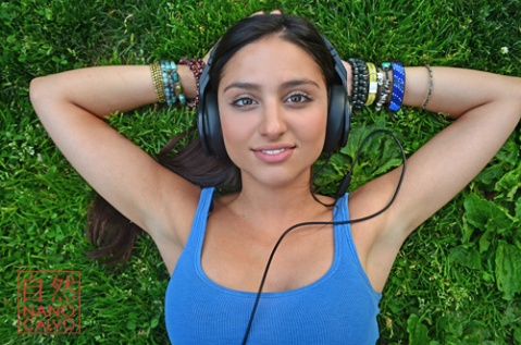 Attractive young mixed race woman listening to music in Central Park