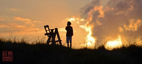 Silhouette of boy and lifeguard chair at sunset